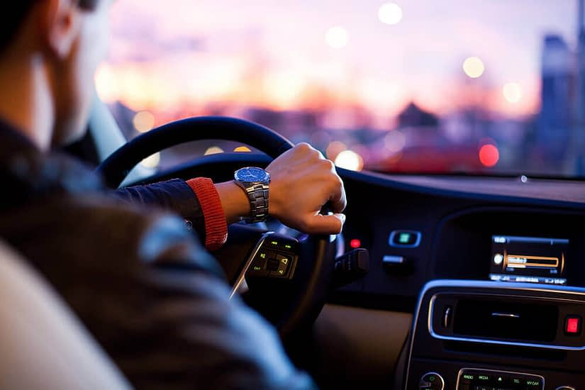 Driver with hand on steering wheel