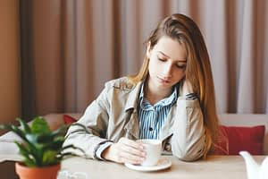 Unemployed woman sits alone heartbroken at a coffee shop