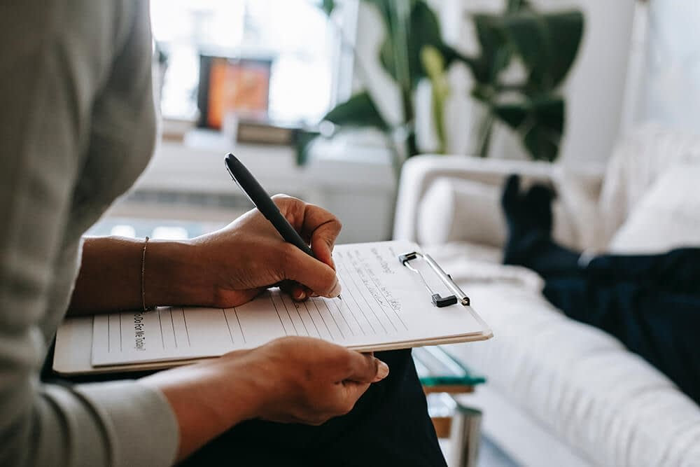 Therapist taking notes with patient on couch