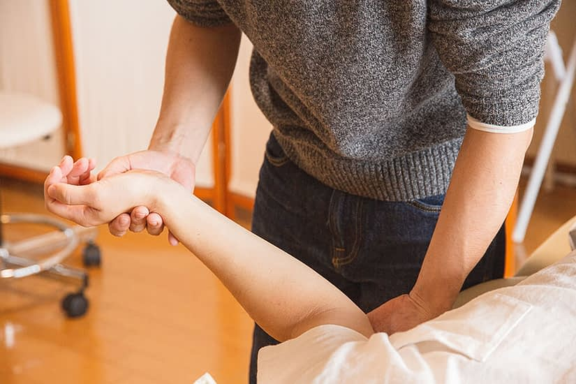 Person treating patient's arm